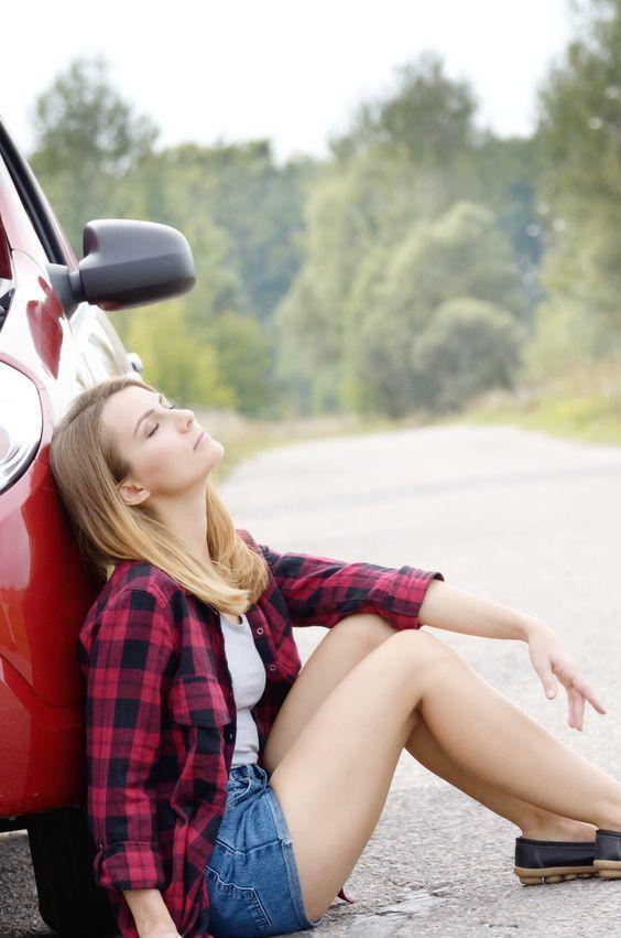 Frau verzweifelt vor Auto